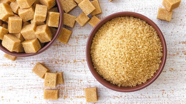 A bowl of brown sugar with sugar cubes on the side