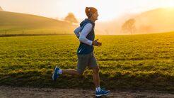 Ein Läufer auf einem Feldweg in der Morgensonne mit Nebel im Hintergrund.