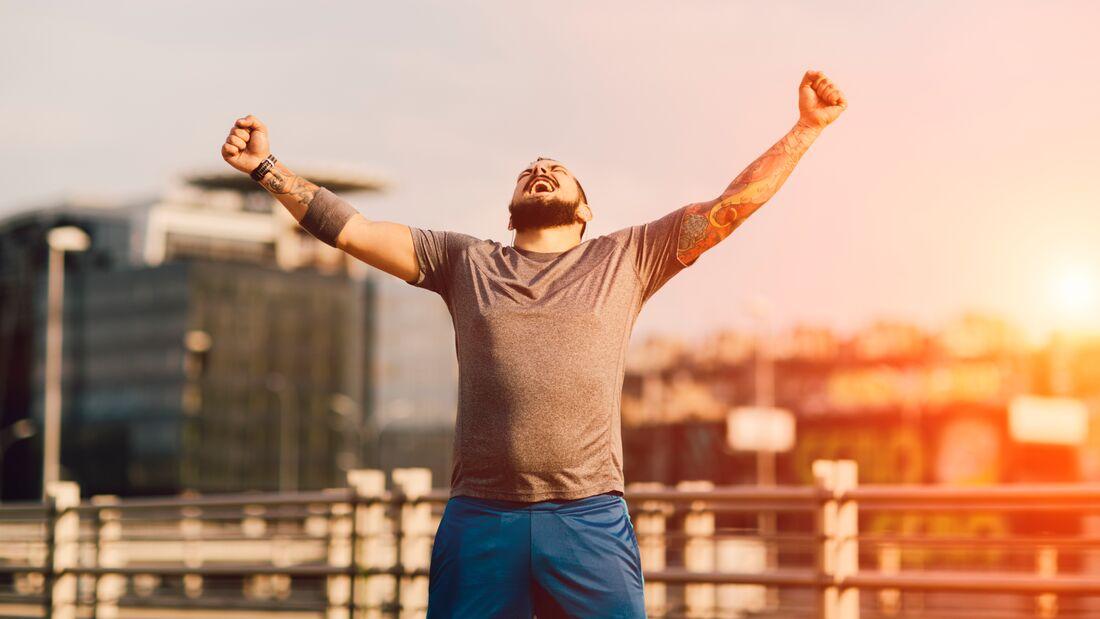 Ein jubelnder Läufer reißt die Arme hoch.