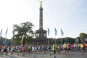 Eine Gruppe Läufer beim Marathon in Berlin um die Friedenssäule