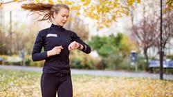 Eine Läuferin schaut auf ihre Pulsuhr