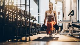 Female athlete exercising with dumbbells in a lunge position at gym.