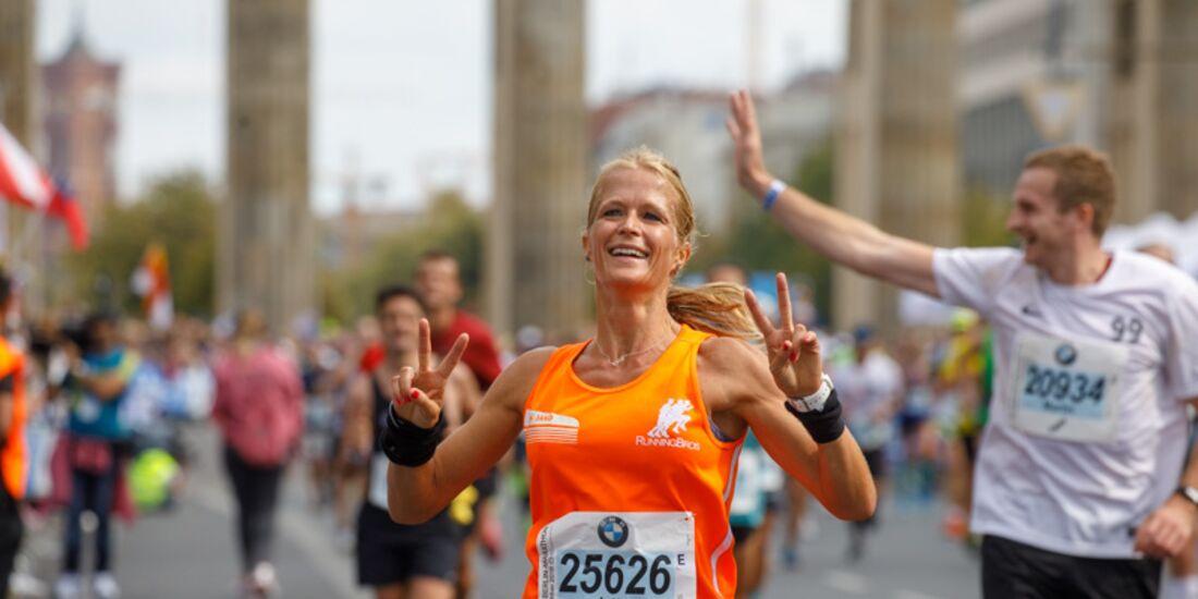 Frau läuft lächelnd einen Straßenlauf