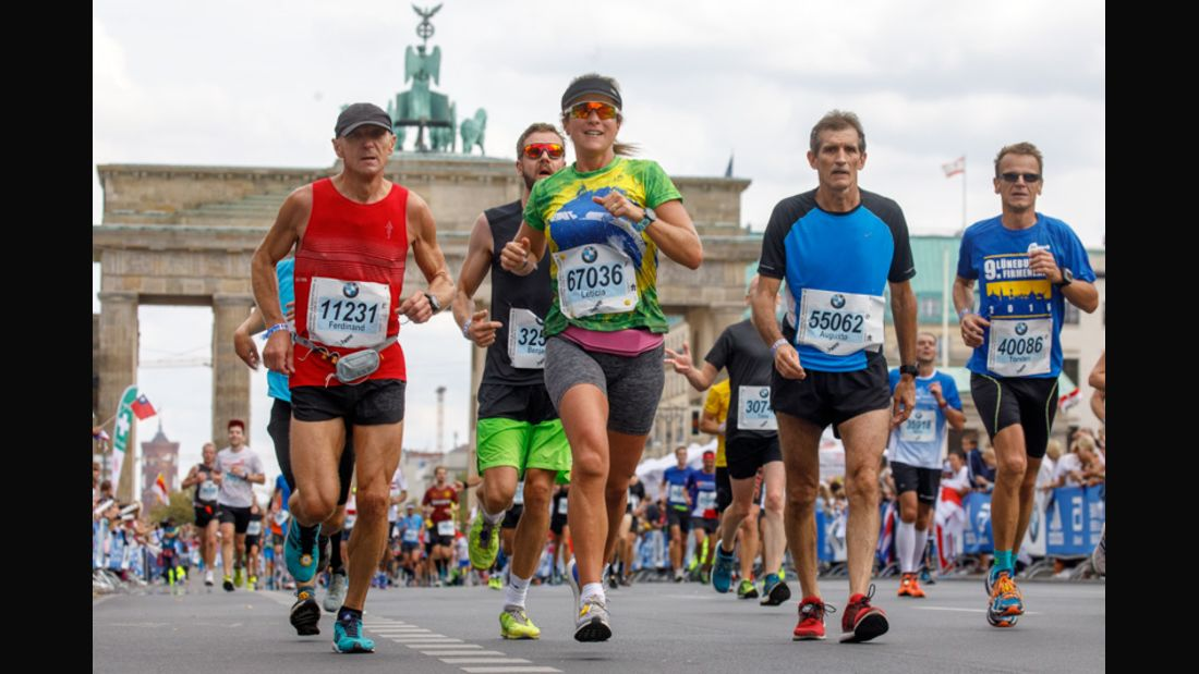 Frau und Männer laufen einen Volkslauf vorm Brandenburger Tor