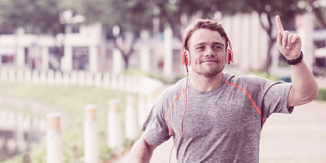 Happy Sportsman Running and Raising Finger in City