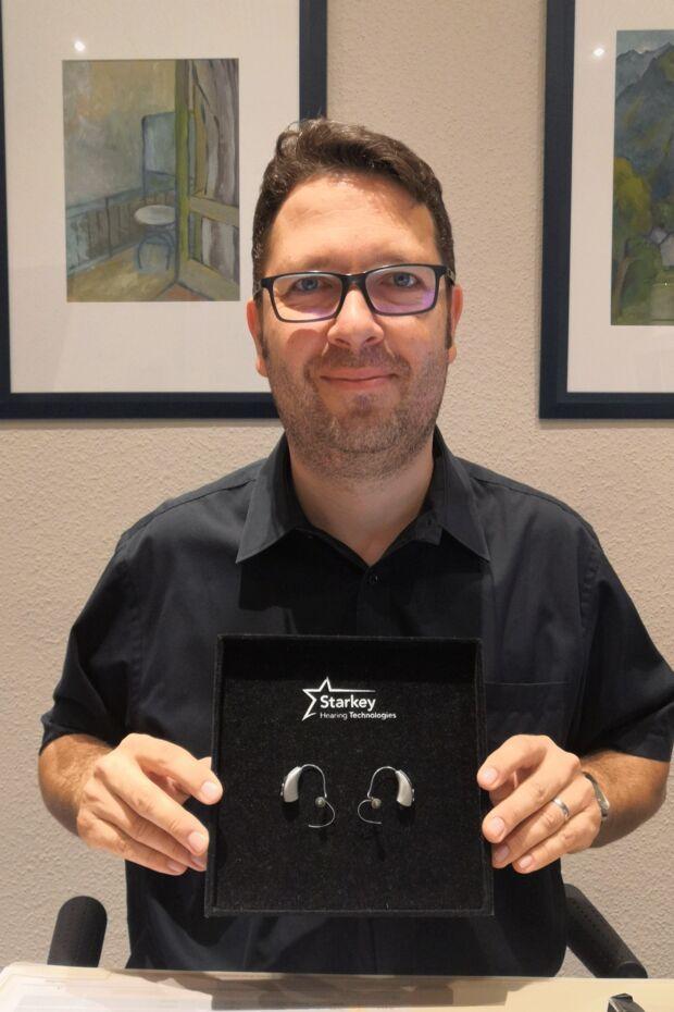 Hörgeräteakustiker Christof Dehn mit dem Hörgerät Livio Al 2400 von Starkey.