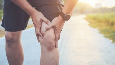Injury from workout concept : Asian man use hands hold on his knee while running on road in the park. Shot in morning time, sunlight and warm effect with copy space for text or design