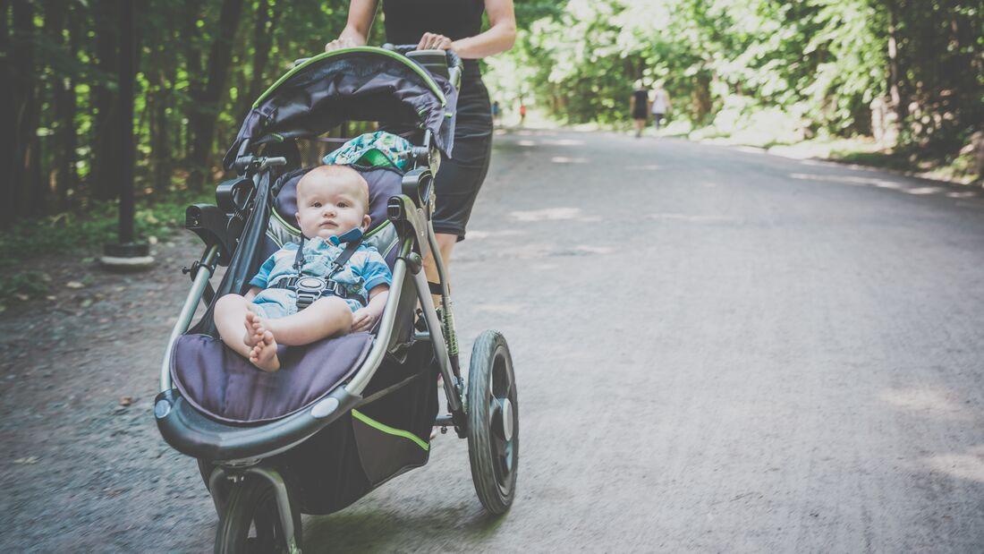 Kleinkind wird in einem Laufkinderwagen geschoben