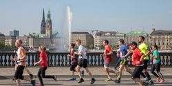 Läufer beim Marathon vor der Binnenalster-Fontäne in Hamburg
