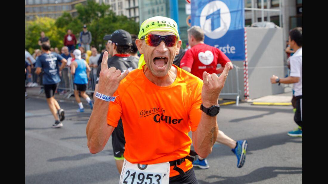 Läufer freut sich beim Laufen mit Handzeichen