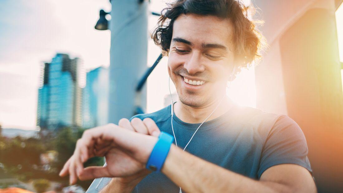 Läufer schaut glücklich auf seinen Tracker