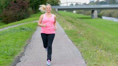 Läuferin auf einem Weg am Fluss