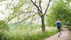 Laeuferin auf einem Weg entlang einer Wiese