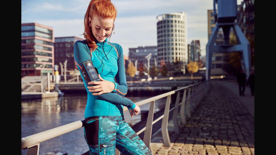 Läuferin schaut auf ihr Smartphone in einer Armtasche