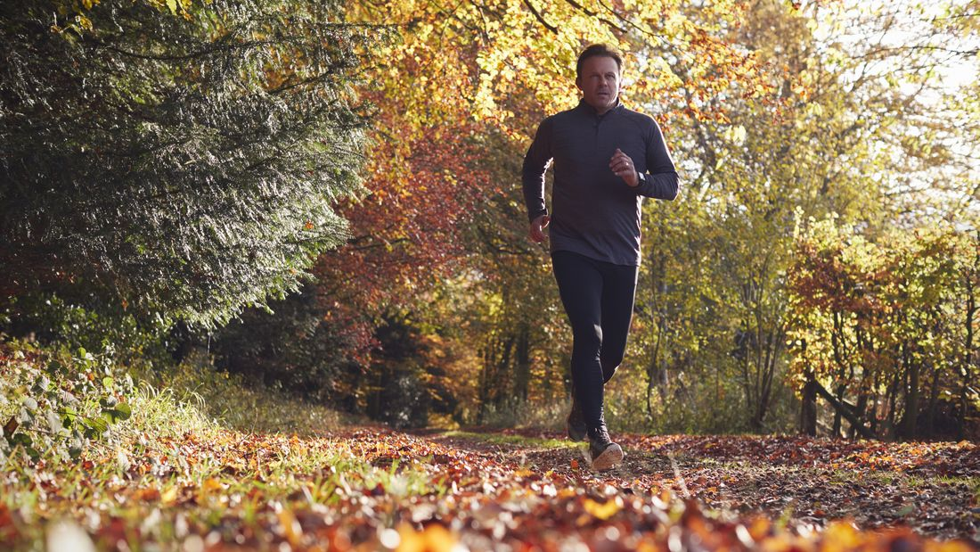 Low Angle View Of Mature Man Running Through Autumn Woodland