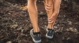 Male runner holding injured calf muscle and suffering with pain. Sprain ligament while running outdoors. View from the back close-up.