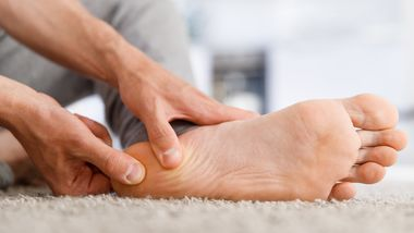 Man hands giving foot massage to yourself after a long walk