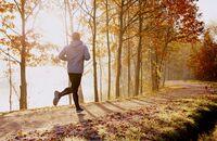 Man running in park at autumn morning