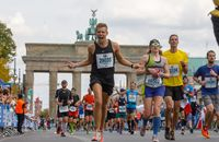Marathonläufer jubelt vorm Brandenburger Tor