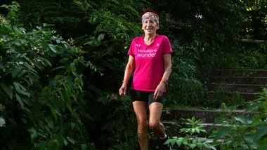 Maria-Luise Kluge läuft lächelnd durch den Wald.