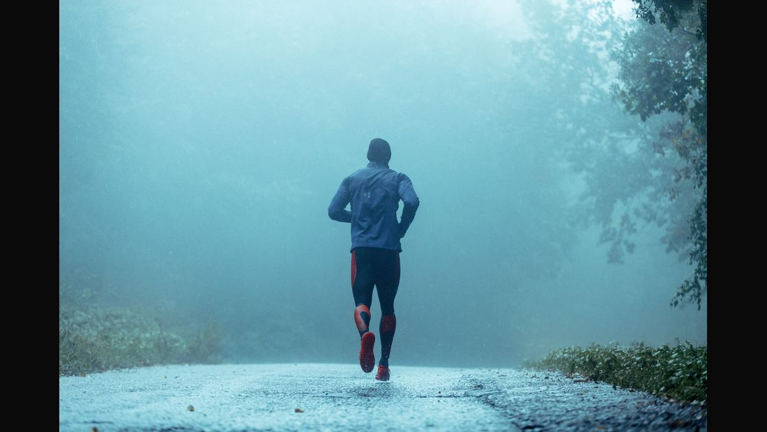 Motivated young man running in the rain.