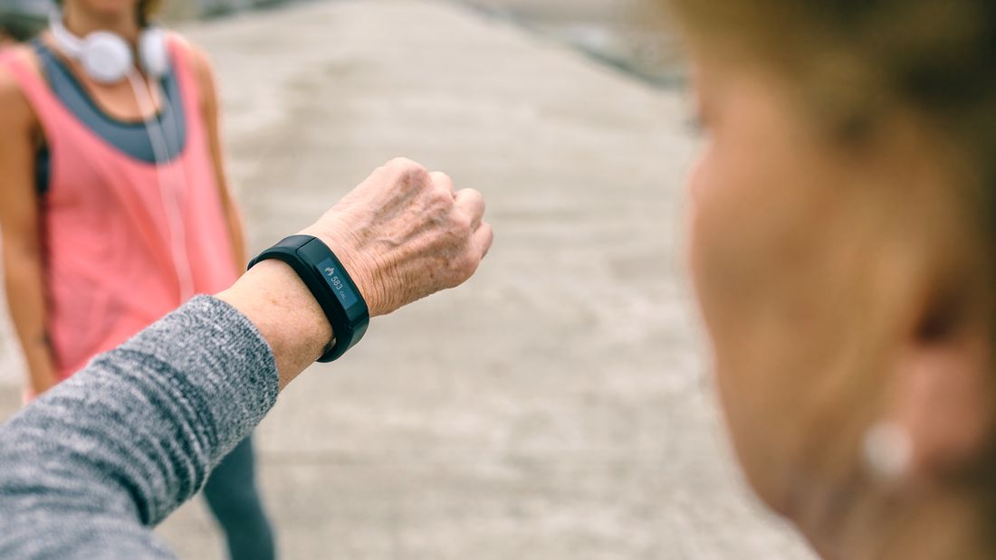 Senior woman looking smart watch with female coach
