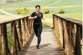 Simone läuft glücklich über eine Holzbrücke