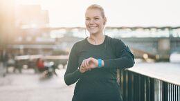Smiling sportswoman checking her smart watch