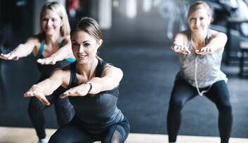 Sportlerin mit orangenen Haaren macht Übungen im Fitnessstudio