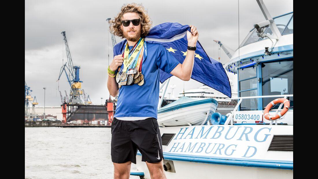Tim Teege im Hamburger Hafen mit einer kleinen Auswahl der Finishermedaillen der letzten Jahre.