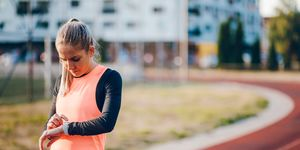 Track runner checking smart watch