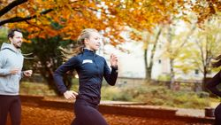 Two young athletes running outside in autumn forest. Aerial view.