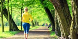 Woman runner running jogging in green summer park and woods