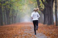 Women in Sport - rear view woman jogging alone in autumn