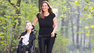 Yasmine Beyaz läuft mit ihrem Sohn, der im Rollstuhl sitzt