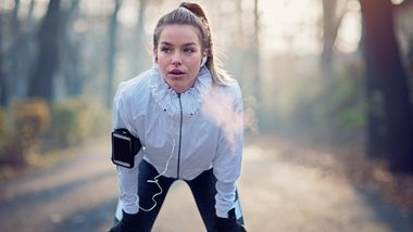 Young girl is resting exhausted after run in foggy morning