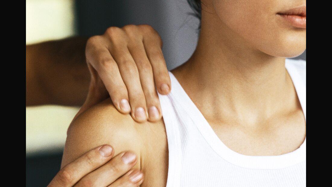 Zwei Hände behandeln die Schulter einer Frau