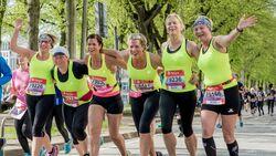 sechs Frauen in gelben Tops Arm in Arm beim Marthonlaufen
